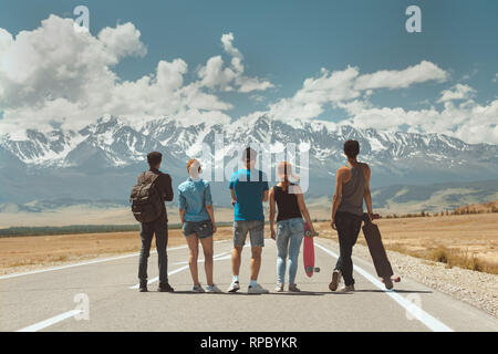 Group of five friends stands on long straight road and looks at mountains. Travel concept - Stock Image