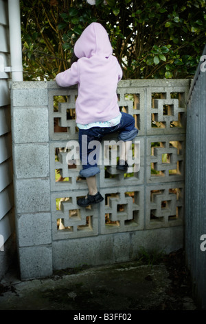 Over the wall Five year old girl clambers over a low garden wall - Stock Image