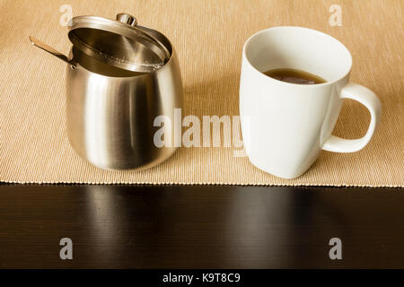 Overhead view of a cup of coffee and a bowl of granulated sugar with a plastic white spoon. Horizontal format on - Stock Image
