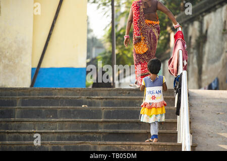 A little girl wearing a colorful dress is climbing the stairs behind her mother who dresses the Sari, a traditional Indian dress. Varanasi, India. - Stock Image