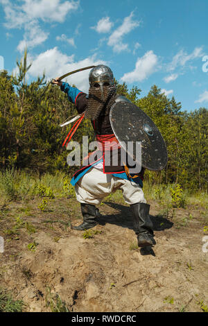 Mongol horde warrior in armour, holding traditional saber. - Stock Image