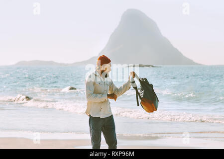Man with backpack walking on ocean beach solo traveling outdoor journey vacations fashion lifestyle - Stock Image