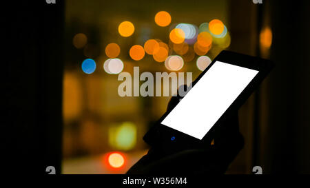 Woman looking at smartphone with white empty display - Stock Image