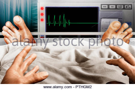 Frightened man in hospital bed seeing flatline pulse trace on monitor - Stock Image