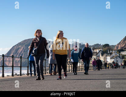 Sidmouth, 29th Oct 18 People out on the Esplanade at Sidmouth on a cold but bright sunny day. Clear overnight skies left a sharp frost across Devon this morning. Photo Central/Alamy Live News - Stock Image