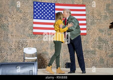 U.S. President Donald Trump kisses First Lady Melania Trump as they take the stage to address U.S. service members during a surprise visit to Al Asad Air Base December 26, 2018 in Al Anbar, Iraq. The president and the first lady spent about three hours on Boxing Day at Al Asad, located in western Iraq, their first trip to visit troops overseas since taking office. - Stock Image