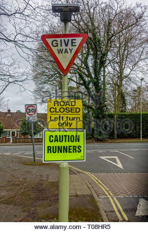 Caution Runners, road closed sign in preparation for the Fleet half-marathon. - Stock Image