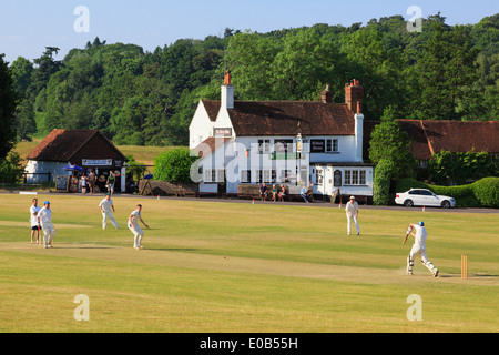 Local teams playing a cricket match on a village green in front of Barley Mow pub on a summer's evening. Tilford Surrey England UK - Stock Image