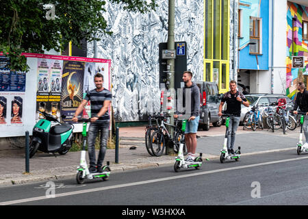 Tourists on e-scooters; In Friedrichshain-Berlin. The electric scooter is the latest form of transport in Germany.; E-scooters have recently been made legal for street use in Germany and are making an appearance in Berlin. Use is restricted to bike lanes & streets. The maximun speed allowed is 20kpm and under- fourteens are not permitted to use the scooters. - Stock Image
