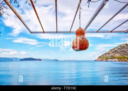 Decorative calabash gourd lantern hanging against the sea and sky background in gumusluk, bodrum, turkey. - Stock Image