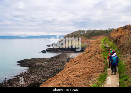 Hikers hiking on a boardwalk along the island of Anglesey Coast Path near Benllech, Isle of Anglesey, Wales, UK, Britain. - Stock Image