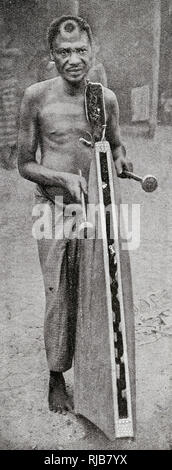 Tribesman playing a tattoo on a percussion instrument to welcome a guest, French Congo, Central Africa. - Stock Image