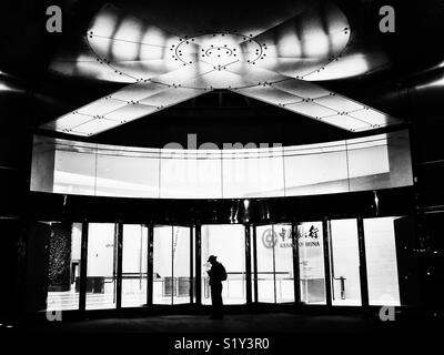 Silhouette of man standing outside of Bank of China in New York City, USA - Stock Image