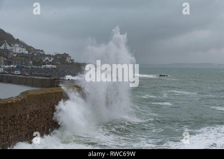 Mousehole, Cornwall, UK. 6th March 2019. UK Weather. A strong swell. following on from storm Freya continues to pound the coast of Cornwall this morning, pushing waves over the harbour wall at Mousehole. Credit: Simon Maycock/Alamy Live News - Stock Image