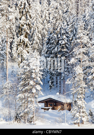 Small wooden sauna cottage in the forest at Winter , Finland - Stock Image