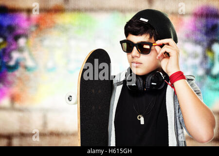 Portrait of a handsome skateboarder wearing sunglasses and stylish hat outdoors, active stylish teen - Stock Image