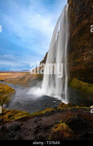 Seljalandsfoss is a waterfall that you can fully walk behind, situated on the South Coast of Iceland with a drop of 60 metres (200 feet). Due to the w - Stock Image