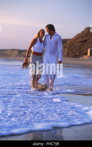 Couple in love enjoying romantic walk through beach waves along California shore at sunset - Stock Image