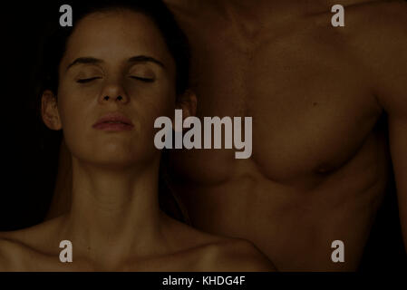 Young woman leaning against man's bare chest with eyes closed - Stock Image