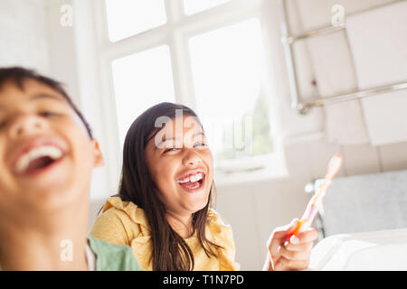 Portrait laughing brother and sister brushing teeth in bathroom - Stock Image
