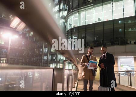 Businessmen with suitcase discussing paperwork on urban pedestrian bridge at night - Stock Image