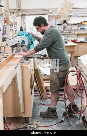 Caucasian male carpenter using a radial saw to cut a piece of wood in a large woodworking factory. - Stock Image
