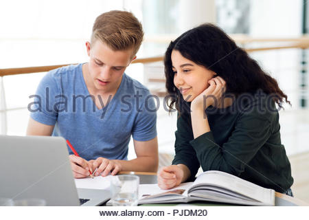 Two high school students at classroom desk working on laptop - Stock Image