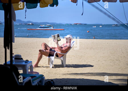 Man sunbathing at the beach, reading a book, sat on a plastic chair - Stock Image