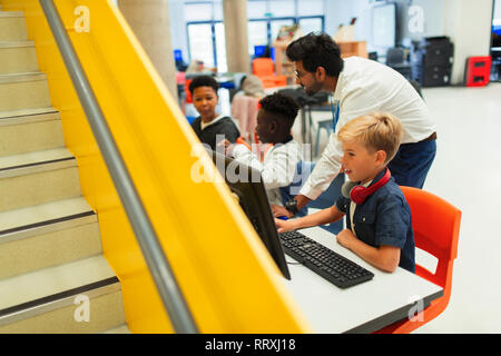 Teacher helping junior high students using computers in library - Stock Image