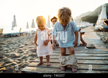 A young family with toddler children having fun on beach on summer holiday. - Stock Image