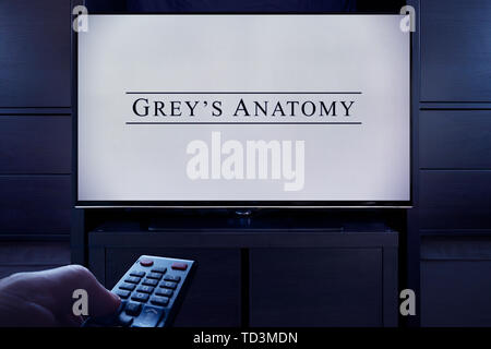 A man points a TV remote at the television which displays the Grey's Anatomy main title screen (Editorial use only). - Stock Image