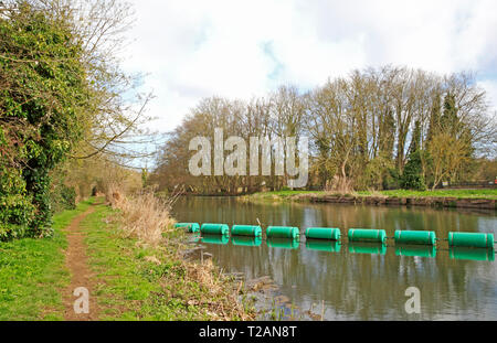 A view of the River Bure with boom and riverside footpath upstream of the old mill at Horstead, Norfolk, England, United Kingdom, Europe. - Stock Image