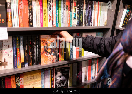 A woman selecting a paperback book from a bookshelve in a Waterstones bookshop - Stock Image