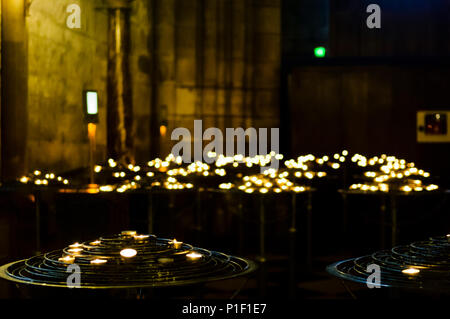 Lit candles in Notre Dame Cathedral in Paris.  Shallow depth of field, with bokeh on candles in the background.  Dark, moody, image with copy space. - Stock Image