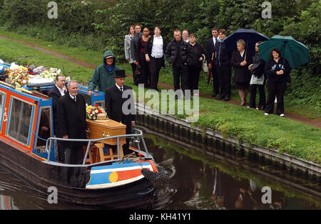Mourners watch narrowboat carrying coffin on canal near Wolverhampton Uk - Stock Image