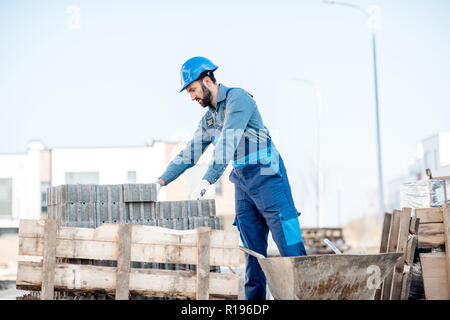 Builder in uniform taking paving blocks from the pallet working on the construction site outdoors - Stock Image