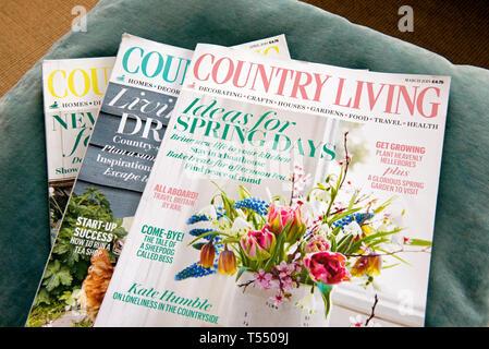 Three Country Living magazines on velvet cushion - Stock Image