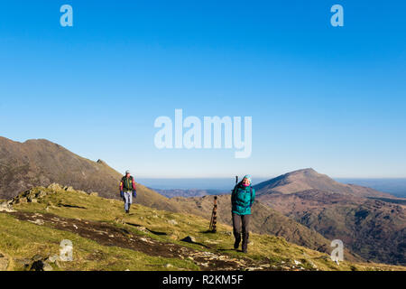 Two hikers on summit of Yr Aran mountain with scorched ground scene of helicopter fire in Snowdonia National Park. Gwynedd, Wales, UK, Britain - Stock Image