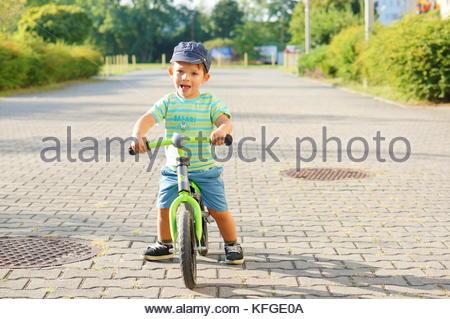 Young toddler boy riding a balance bike on a sidewalk - Stock Image