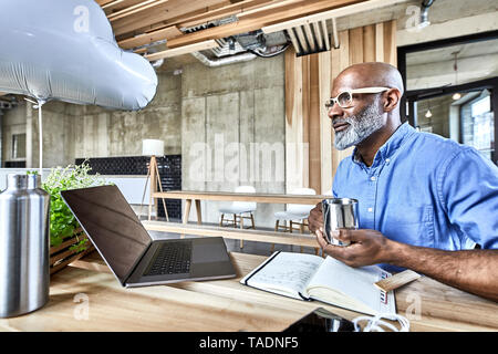 Mature businessman sitting at table in modern office with cloud balloon and laptop - Stock Image
