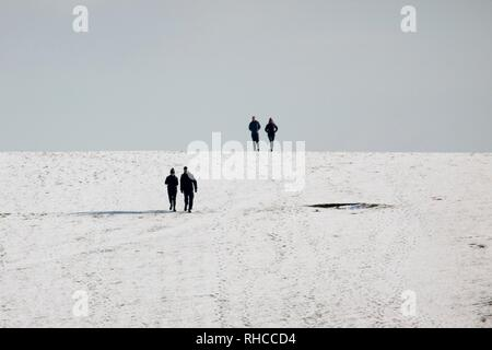 Beachy Head, UK. 2nd Feb 2019.UK weather.Day trippers enjoy walking on the snow covered hills of Beachy Head this morning. East Sussex, UK. Credit: Ed Brown/Alamy Live News - Stock Image