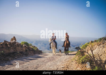 outdoor cowboy life couple ride horses at the mountain enjoying excursion in the nature together - alternative vacation travel lifestyle for alternati - Stock Image