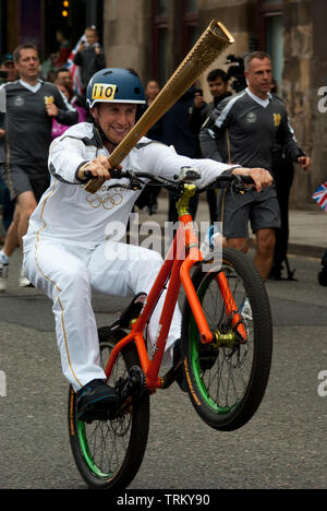 Danny Macaskill carried the Olympic torch through the streets of Glasgow on day 21 of the 70-day relay. The rider started at Kelvingrove Art Gallery - Stock Image