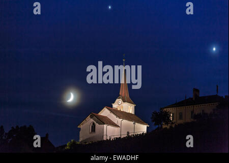 Fechy, Switzerland 20 June. A conjunction of Venus, Jupiter and the Moon in the evening sky over Fechy church. In - Stock Image
