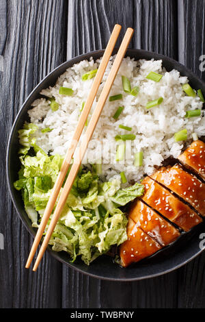 Portion of teriyaki chicken fillet with rice and lettuce close-up on a plate on the table. Vertical top view from above - Stock Image