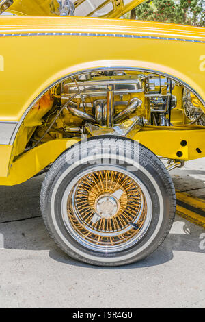 A detail of one of the wheel wells of a bright yellow Chevrolet lowrider car that has been completely customized showing the 13 inch wire wheels and a - Stock Image