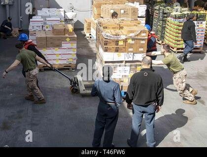 MEDITERRANEAN SEA (Mar. 9, 2019) - U.S. Marines and Sailors with the 22nd Marine Expeditionary Unit and the San Antonio-class amphibious transport dock ship USS Arlington (LPD-24) help each other move pallets of stores across the boat valley of the Arlington during a replenishment-at-sea, Mar. 9, 2019. The USS Arlington is making a scheduled deployment as part of the 22nd MEU and the Kearsarge Amphibious Ready Group, in support of maritime security operations, crisis response and theater security cooperation, while also providing a forward Naval and Marine presence. - Stock Image