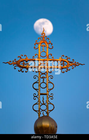 Cross in front of a waxing gibbous moon - Stock Image
