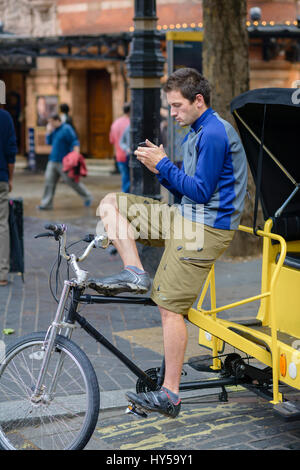 Young male London pedicab driver (rickshaw rider) checks his mobile phone while waiting for his next fare. Young - Stock Image
