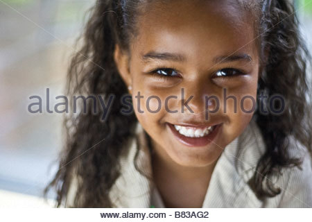 pretty young black girl aged 4 5 smiling and looking excited - Stock Image